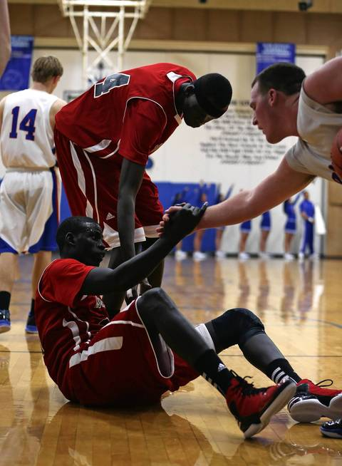 Mooseheart's Mangisto Deng is helped up by teammate Akim Nyang and Hinckley-Big Rock's Zack Michels during Mooseheart's 58-51 loss in Hinckley.