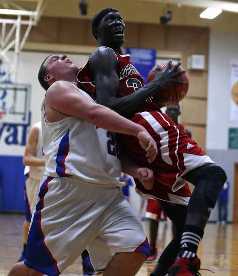 Mooseheart's Makur Puou is fouled by Hinckley-Big Rock's Zack Michels during Mooseheart's 58-51 loss in Hinckley. Puou scored 25 points in the loss.