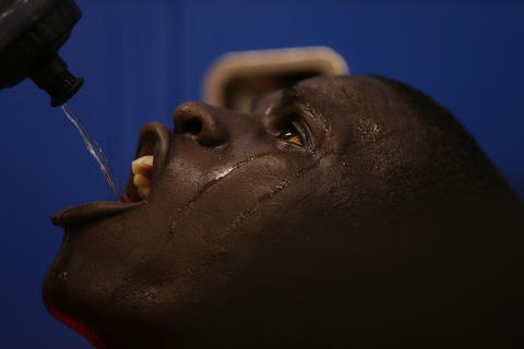 Mooseheart's Mangisto Deng takes a drink of water during halftime of 58-51 loss to Hinckley-Big Rock in Hinckley, Ill.