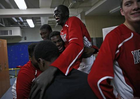 Mooseheart basketball players from the Sudan, Akim Nyang and Mangisto Deng and Makur Puou, celebrate with with their teammates in the visiting locker room at Hiawatha High School in Kirkland after the IHSA determined they are eligible to play.