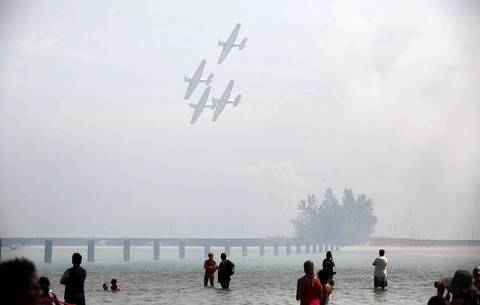 The Aeroshell Aerobatic Team flies over people swimming at the North Avenue beach during the 54th annual Air and Water Show in Chicago.