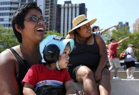 Bianca Cabrera of Chicago sits with her 18-month-old son, Oliver, during the second day of the 54th annual Air and Water Show in Chicago.