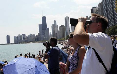 Zach Dismukes of Chicago uses binoculars during the second day of the 54th annual Air and Water Show in Chicago.