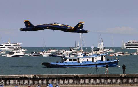U.S. Navy Blue Angels jets pass each other traveling in opposite directions at low altitude, flying over boats bobbing in Lake Michigan during the Chicago Air and Water Show at North Avenue Beach.