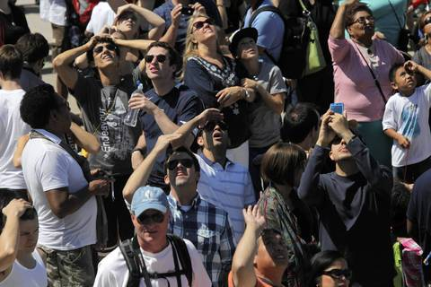 Members of the audience watch an F-4 Phantom fly over during the Chicago Air and Water Show at North Avenue Beach.