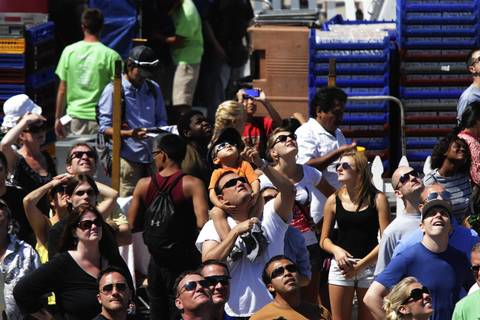 People look up to see the U.S. Navy Blue Angels perform air maneuvers at the Chicago Air and Water Show.