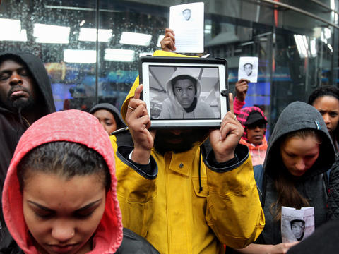 Jayve Montgomery, holding an electronic picture of Trayvon Martin, was among hundreds of people who marched in the Loop in support of the slain 17-year-old's family. Martin was unarmed when he was fatally shot in February in Sanford, Fla. Go here to read our story.