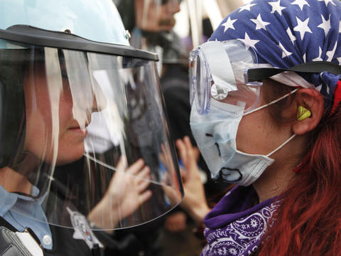 A protester faces off with a Chicago police officer in riot gear at Cermak Road and Wabash Avenue, near the flash point of clashes that day during the 2012 NATO summit. Go here to see our photogallery.