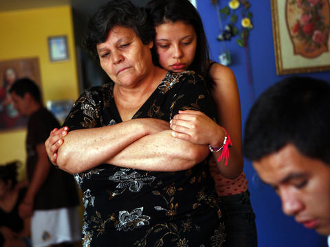 Angelica Mora, whose father was killed in an attack July 10, hugs her mother, Maria Carmen Mora, at their Far North Side home. Delfino Mora, a father of 12, was collecting cans in an alley when he was attacked by three teens. Go here to read the story.