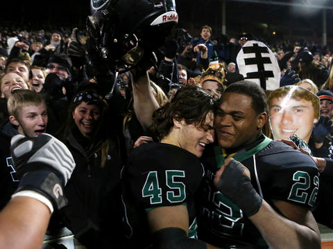 Glenbard West's Jordan Hassan (45) and Devante Toney (22) celebrate with fans and teammates after edging Lincoln-Way East 10-8 to win the 7A State Championship at Memorial Stadium in Champaign. Click here to see more photos from the game.