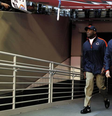 Lovie Smith walks out before the game.