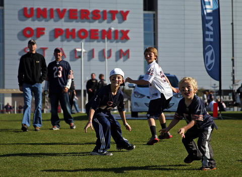 Bears fan Jake Taylor, 8, and his brothers Wyatt, 11, and Ace, 5, wait for a football to be thrown to them outside University of Phoenix Stadium.