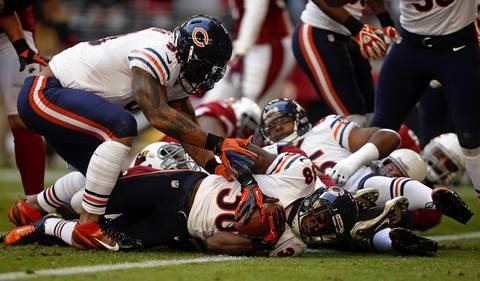 Zack Bowman picks up a fumble for a touchdown against the Cardinals in the first quarter.