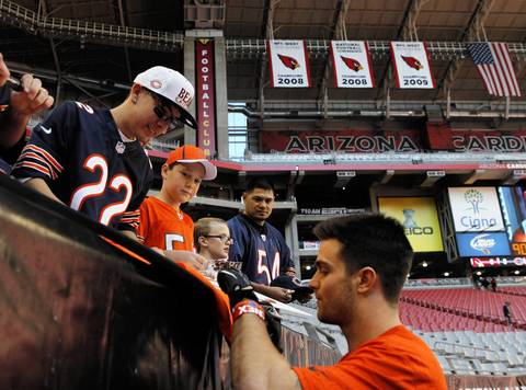 Safety Chris Conte signs autographs for fans before the game.