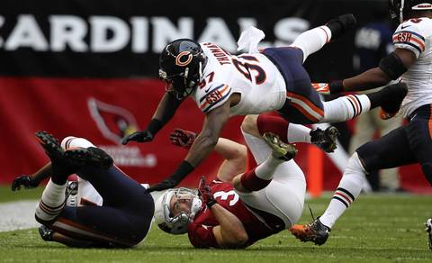 JT Thomas flies over the Cardinals' Jay Feely after a failed fake field goal in the 2nd quarter.