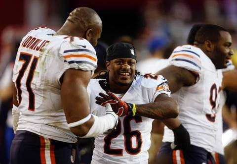 Israel Idonije and Tim Jennings celebrates on the bench as they defeat the Cardinals in the fourth quarter.