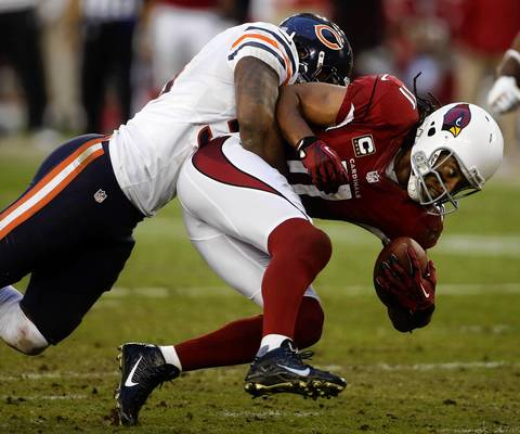 Linebacker Nick Roach tackles Cardinals wide receiver Larry Fitzgerald in the fourth quarter.