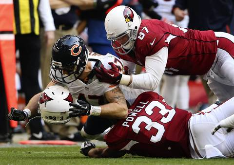 Chris Conte tackles the helmet of the Cardinals' William Powell in the 2nd quarter.