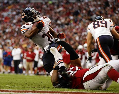 Running back Armando Allen is tackled by the Cardinals' Dan Williams in the third quarter.