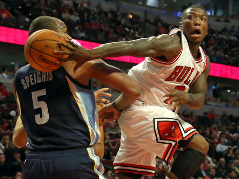 Bulls guard Nate Robinson makes a pass around Grizzlies forward Marreese Speights during the first half of a preseason game at the United Center.
