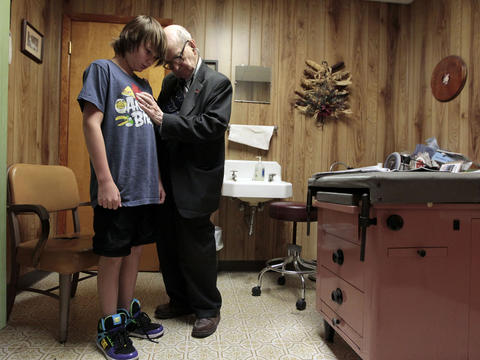 "Dr. Russell Dohner, 87, gives Austin Clark, of Macomb, a sports eligibility exam at his office in Rushville, Ill. Dohner charges $5 for office visits, the same rate he has charged since the 1970s. ""I never went into medicine to make money,"" Dohner says. ""I wanted to be a doctor, taking care of people."" For more on Dr. Dohner: Go here to watch a video about him. 