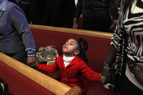 Brenette Garland, 6, prays during a service lead by Rev. Otis Moss III, senior pastor at Trinity United Church of Christ on Jan. 15.