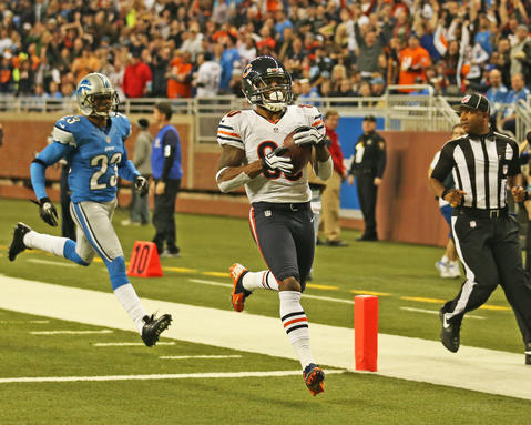 Wide receiver Earl Bennett finishes a 60-yard touchdown run against the Lions during the first quarter. Behind him is Lions cornerback Chris Houston.