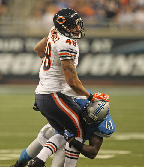 Evan Rodriguez is tackled by Lions cornerback Ron Bartell during the first quarter.