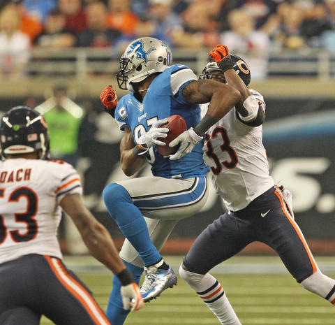 Lions wide receiver Calvin Johnson makes a catch in front of cornerback Charles Tillman during the first quarter.