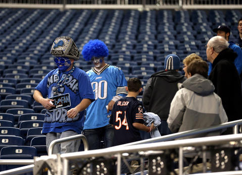 Arriving Lions fans pass by Bears fans before a game at Ford Field in Detroit on Sunday.