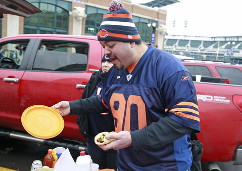 Ruben Silvas of Chicago makes himself a taco while tailgating before the game.