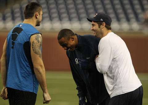Quarterback Jay Cutler and wide receiver Brandon Marshall laugh with Lions tight end Tony Scheffler.