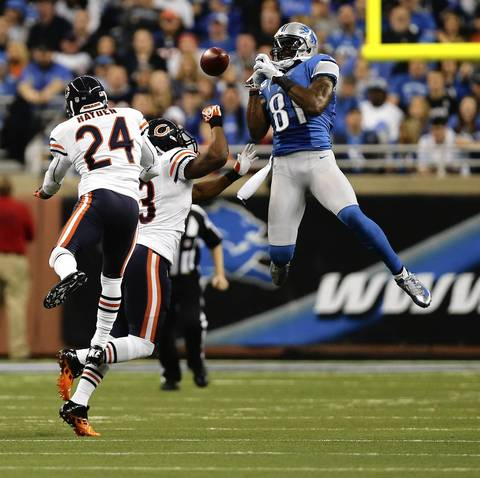 Lions wide receiver Calvin Johnson can't come up with a pass as Nick Roach and Kelvin Hayden defend in the second quarter.