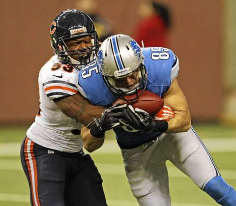 Nick Roach stops Lions tight end Tony Scheffler after he made a catch during the second half.