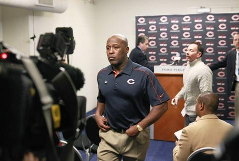 Lovie Smith walks away from the podium after his press conference at the end of his team's win.