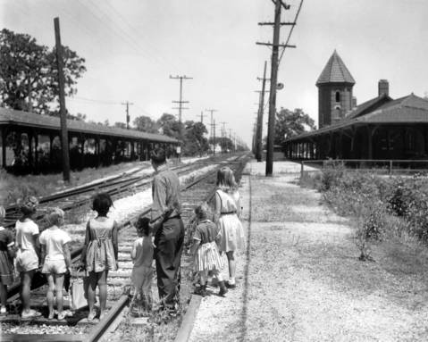 The deserted North Shore line depot at Salem Blvd. in Zion, Ill., which was the finest on the electric line from Milwaukee to Chicago, was built of brick with a spiral tower and had a long loading platform. Ward Wilson points out the abandoned railroad to his three daughters and other neighborhood children in the summer of 1964, a year after the rail line shut down.