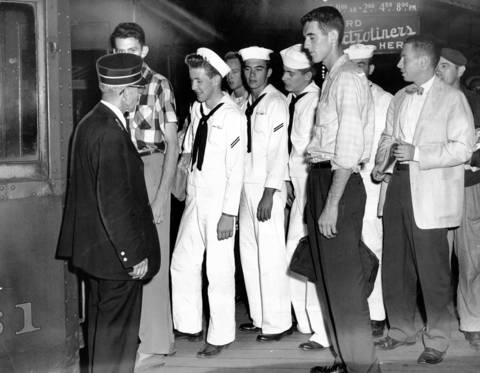 Conductor Leslie Greenfield watches a group of Great Lakes Naval Training Center sailors board the last train at 12:45 a.m. of the North Shore line, leaving Adams and Wabash stations. Sailors from the base were some of the North Shore's best customers. The railroad shut down in 1963.