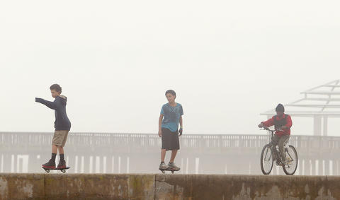 Brothers Vinny and Giovanni Lester and Christopher Chapman play on the seawall at Buckroe Beach Saturday morning as a heavy fog blankets the Peninsula.