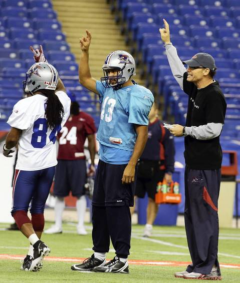 Montreal Alouettes' quarterback Anthony Calvillo (C) signals with coach Marc Trestman during practice in Montreal.