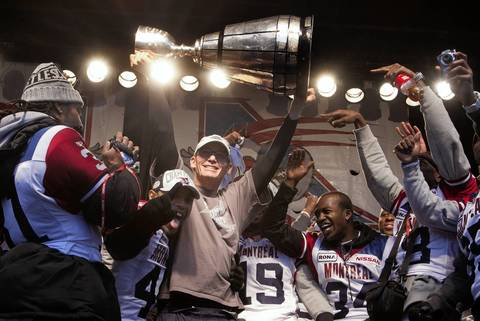 Montreal Alouettes' coach Marc Trestman (C) holds up the Grey Cup as he celebrates during the team's victory parade in Montreal.