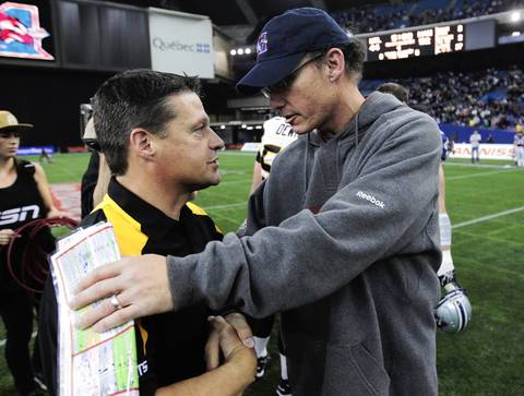Montreal Alouettes' head coach Marc Trestman (R) congratulates Hamilton Tiger-Cats' head coach Marcel Bellefeuille (L) on their win following overtime action of their CFL Eastern semi-final football game in Montreal.