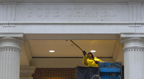 Alfredo Noriega cleans the exterior of Pope Chapel early Thursday as workers put the finishing touches on the structure. The 14,000-square foot structure is scheduled to open this month and is located between the Trible Library and Ferguson Center for the Arts.