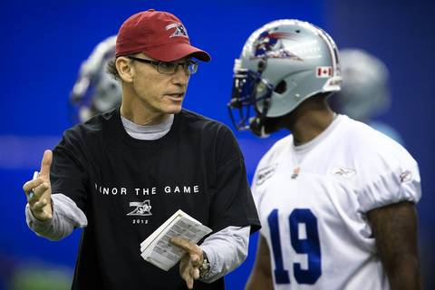 Montreal Alouettes head coach Marc Trestman, left, speaks to players during practice for their upcoming CFL game against the Toronto Argonauts at the Olympic Stadium in Montreal.