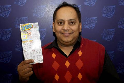 Urooj Khan holds his winning $1 million lottery ticket.