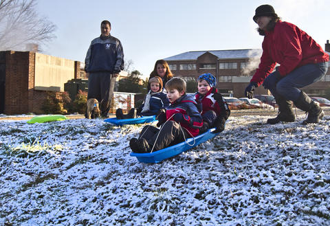 Tara Chicirda gives a push to Ryan Chicirda 6 and Wyatt Bradley 5 as they enjoying some time sledding near the Colonial Parkway.