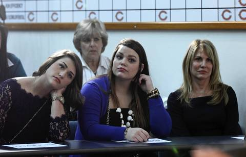 Sisters Chloe and Sarahanne Trestman, from left, with their mother, Cindy, listen to Marc Trestman take questions as the new Chicago Bears head coach.