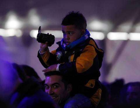 A man holds up a young boy for a better view during a National Day of Service kickoff event on the National Mall.