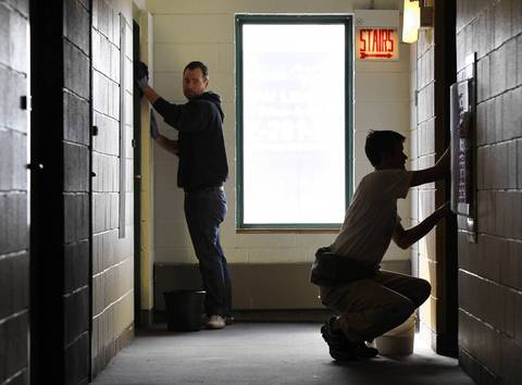 Volunteers Paul Frede, left, and David Watkins clean doors in a hallway at The Studios, an affordable housing building in Chicago, as part of Saturday's Day of Service.