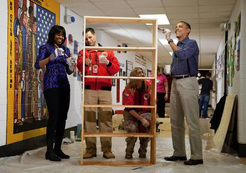 President Barack Obama and first lady Michelle Obama help to stain a bookshelf at Burrville Elementary School in Washington, D.C. Joining the Obamas are Jeff Franco, Executive Director of City Year, and Sheri Fisher, a City Year employee. The event was part of the National Day of Service, the first official event of the 57th presidential inauguration weekend.