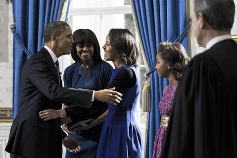 President Barack Obama hugs daughter Malia after being officially sworn-in as the 44th President by Chief Justice John Roberts Jr., right, in the Blue Room of the White House. First lady Michelle Obama and daughter, Sasha join in the ceremony.